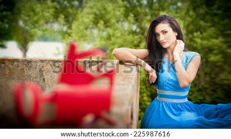 Charming young brunette woman in bright blue dress with red shoes in foreground. Sexy gorgeous fashionable woman, outdoor shot. Portrait of an attractive lady with long hair and red sandals - stock photo