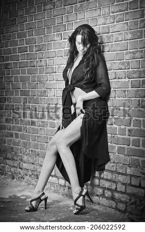 Charming young brunette woman with high heels staying near a brick wall. Sexy gorgeous female against an old wall. Full length portrait of a provocative woman with long hair, black and white photo - stock photo