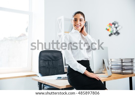 Charming young businesswoman sitting on the table at office