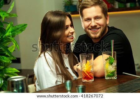 Charming young couple having fun in the bar with alcohol cocktails. Couple smiling behind the bar. Couple in love. - stock photo