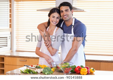 Charming young couple posing in their kitchen - stock photo