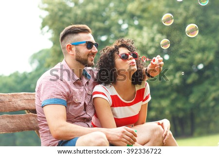 Charming young couple sitting on the bench in the park and blowing bubbles. - stock photo