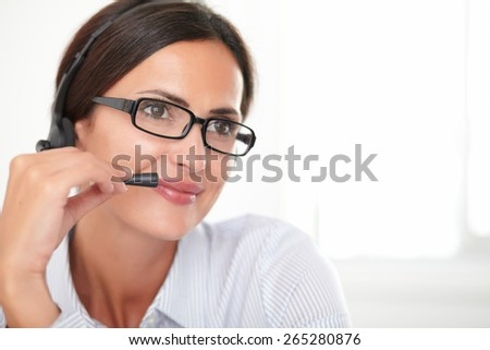 Charming young employee with spectacles conversing on headphones while smiling - stock photo