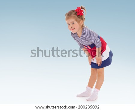 Charming young girl n striped dress and a red bow on her head - stock photo