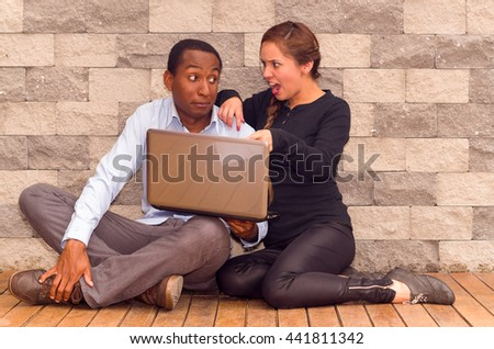 Charming young interracial couple sitting by brick wall with laptop interacting and having fun
