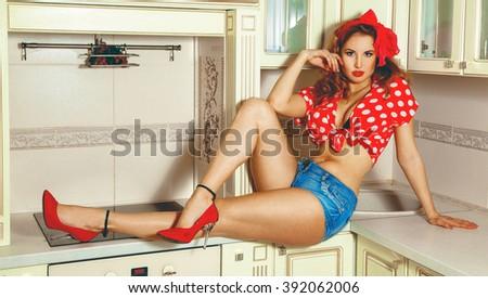 Charming young lady with curly hair in pinup style posing in the kitchen. Pin-up woman. Pin up style woman in the kitchen. Pin up clothes. - stock photo