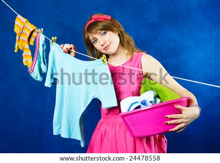 charming young tired housewife hanging clothes on clothesline using clothespin, against blue background - stock photo
