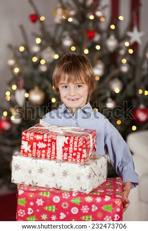 Charming Young White Boy Holding Assorted Christmas Boxes While Smiling at the Camera. Captured Indoor with Lighted Christmas Tree at the Background. - stock photo