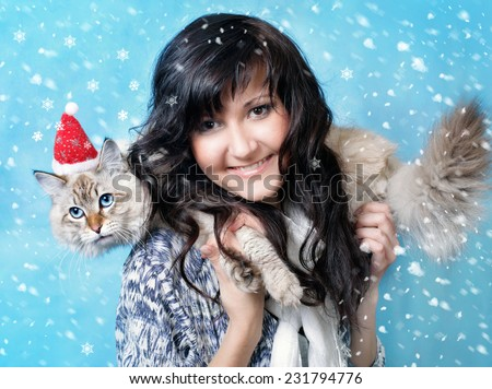 Charming young woman and siberian cat  in santa cap in snow - stock photo