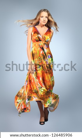 Charming young woman dancing in a vivid summer dress. - stock photo