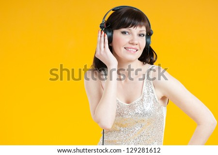 Charming young woman listening to music in headphones - stock photo