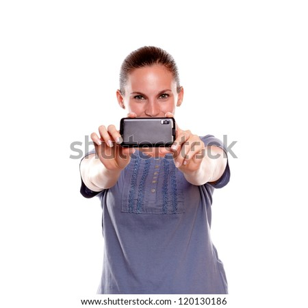 Charming young woman taking a photo with cellphone on blue shirt standing over white background - stock photo