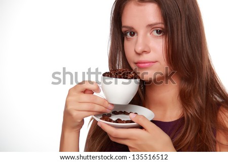 Charming young woman with a beautiful smile holding a white coffee cup full of coffee beans on a white background on Food and Drink