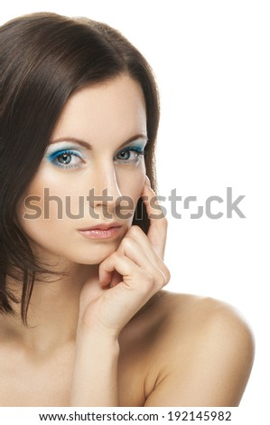 Charming young woman with bared shoulders has brought forefinger to mouth and looks up, reflecting on the life. - stock photo