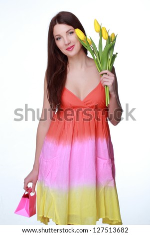 Charming young woman with beautiful long hair in a summer dress with fresh yellow tulips and pink box/Happy girl holding a bouquet on Holiday