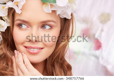 Charming young woman with natural make-up looking sideways - stock photo