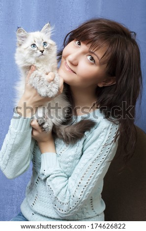 Charming young woman with sibirsky nevsky kitten