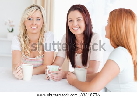 Charming young Women sitting at a table with cups in a kitchen