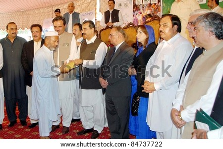 CHARSADDA, PAKISTAN - SEPT. 15: Prime Minister, Syed Yousuf Raza Gilani distributes  Watan Cards among flood affectees of Charsadda District during ceremony on September 15, 2011 in Charsadda, Pakistan.