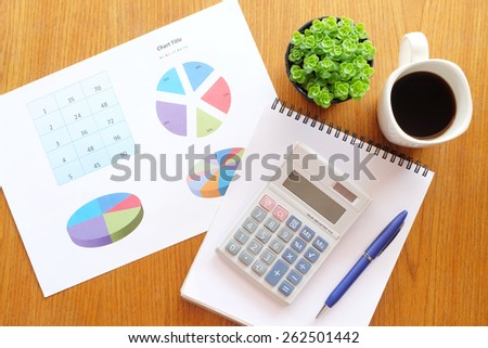 chart and calculator on the wooden table with hot coffee - stock photo