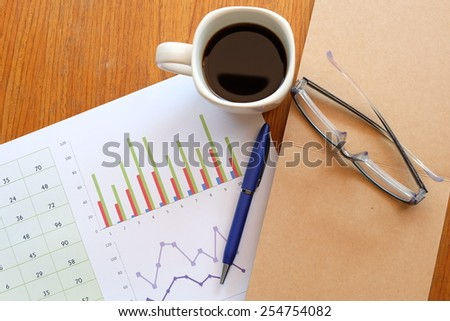 chart and note book on the wooden table with back coffee   - stock photo