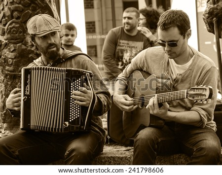 CHARTRES, FRANCE - APRIL 14, 2013: Two undefined street musicians and the public. Hundreds of buskers perform on the streets in France. - stock photo