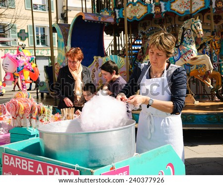 CHARTRES, FRANCE - APRIL 14, 2013: Unidentified vendor prepares candy cotton and the costumers choosing sweets. Cotton candy is one of the most sold sweets at the fairs.  - stock photo