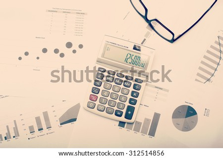 Charts and statistics on desktop with calculator and pen, viewed from above. - stock photo