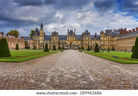 Chateau de Fontainebleau on a cloudy day, residence of Napoleon I, Paris, France  - stock photo