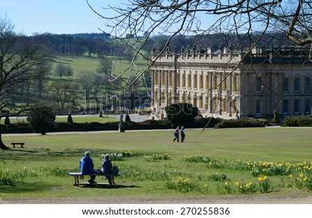 CHATSWORTH HOUSE, BAKEWELL, DERBYSHIRE, ENGLAND - APRIL 14: A middle aged couple sit on bench in gardens of Chatsworth House. At Chatsworth House, Bakewell, England on 14th April 2015. - stock photo