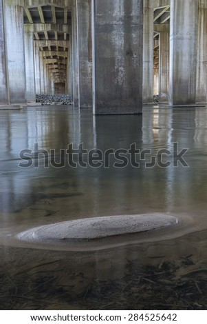 Chattahoochee river flowing under bridge with many concrete supports and a small sand bar. - stock photo