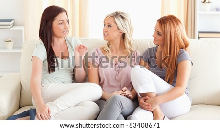 Chatting friends sitting on a sofa in a living room