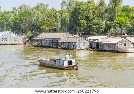 CHAU DOC, VIETNAM - JANUARY 2, 2013: Rural life in Mekong delta- Floating village and fishing boat on Bassac River