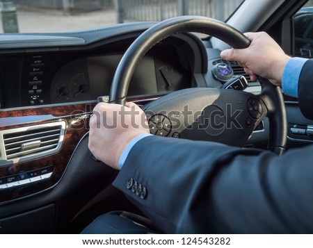 Chauffeur's hands on the steering wheel of a luxury car - stock photo