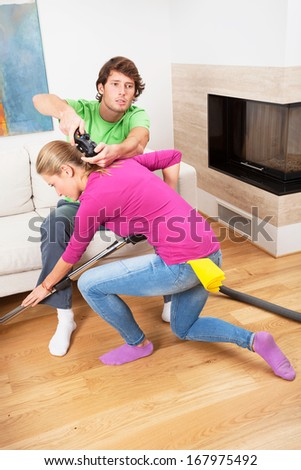 Chauvinist and his hard-working wife with vacuum cleaner - stock photo