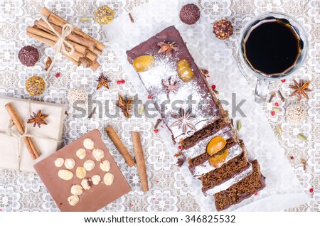 Chcolate spices cake with star anise and dried fruits, cinnamon, cloves, cardamom, handmade milk chocolate with nuts, mulled wine on sackcloth, canvas.  - stock photo