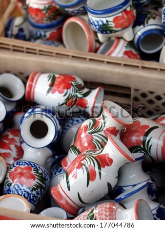 cheap nice colorful earthenware ceramics for home use in a basket on a street market for sale in Thailand - stock photo