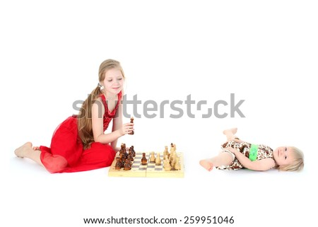 check - adorable little two sisters 9 year and  1  year old play in chess on white background - stock photo