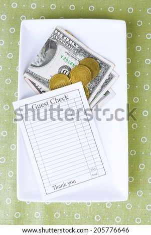 Check and money on tray on table close-up - stock photo