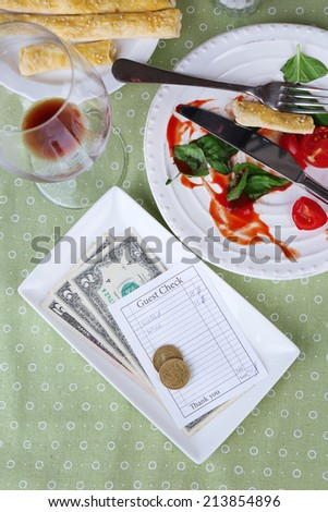 Check and remnants of food and drink on table in restaurant  - stock photo