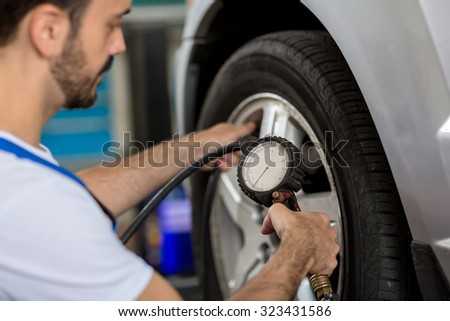 check holding pressure gauge for car tyre pressure measurement - stock photo