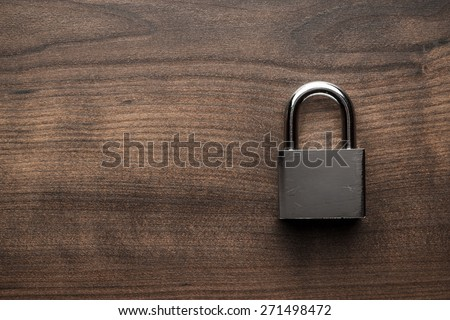check-lock on the brown wooden table background - stock photo