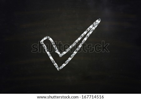 check mark illustration sketched with chalk on blackboard - stock photo