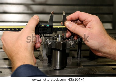 Check measurement of a bore in a metal blank in attachment by hand caliper - stock photo