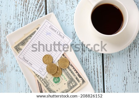 Check, money and cup of coffee on table close-up - stock photo