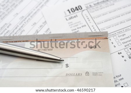 Checkbook and 1040 tax form with pen