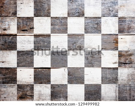 Checkered finish flag painted on grungy wood plank background - stock photo