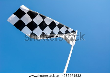 Checkered flag flying on blue sky background - stock photo