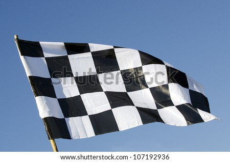 Checkered flag isolated on  blue sky. Concept photo of winner ,winning ,best ,first ,champion , competition , speed, start, starting,finish , finishing,  complete, completing and compete ,