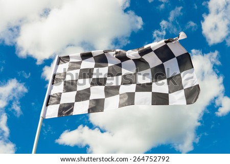 Checkered flag waving in the wind - clouds on background - stock photo